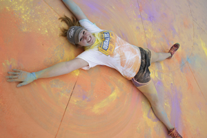 Misericordia student laying on a colorful ground